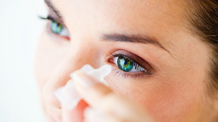 woman putting eyedrops into eye